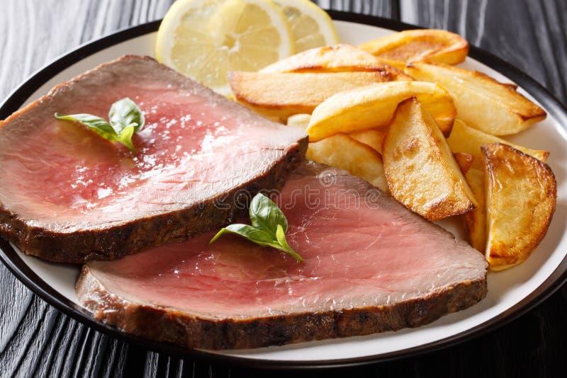 Отрезанный стейк говядины с зажаренным концом-вверх картошки на плите Horiz стоковое фото