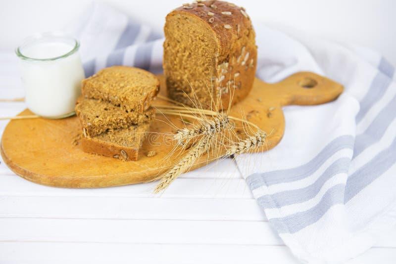 Отрезанный хлеб на деревянной доске, стекле молока, высушенной пшеницы стоковое фото rf