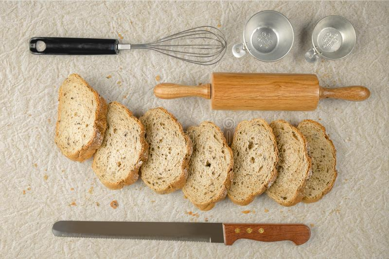 Отрезанный хлеб с инструментами пекарни на бумажной предпосылке стоковая фотография rf
