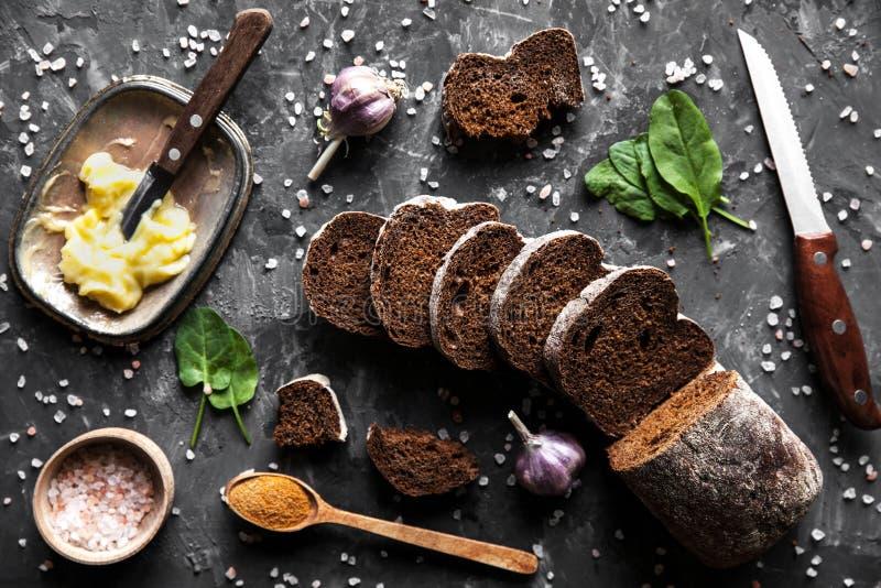 Отрезанный хлеб с маслом и частями разбросал на темную предпосылку стоковая фотография