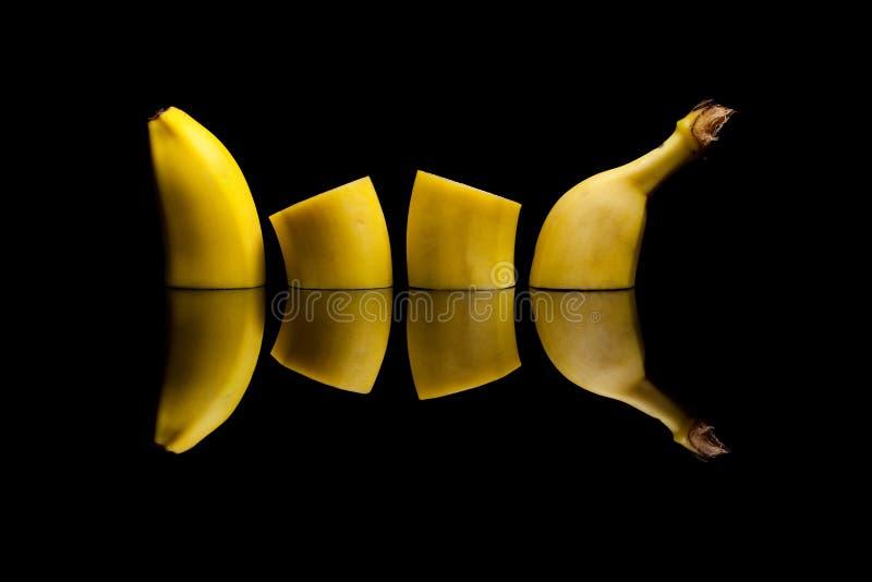 Отрезать желтый банан на черной предпосылке стоковое фото rf