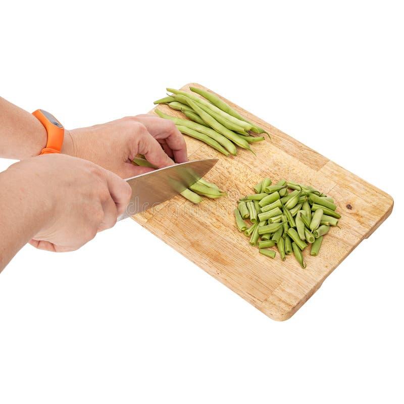 Отрезать свежие зеленые фасоли на разделочной доске на таблице стоковое изображение rf