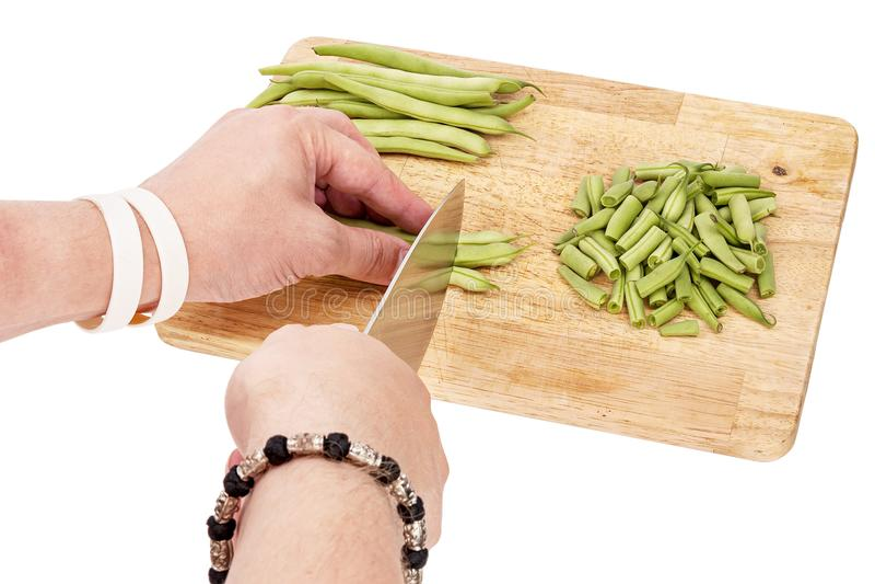Отрезать свежие зеленые фасоли на разделочной доске на таблице стоковые изображения rf