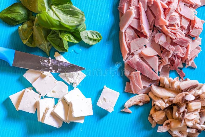 Отрезка ингредиенты вверх как ветчина, гриб, сыр и базилик на голубой пластиковой прерывая доске с коротким острым ножом стоковая фотография