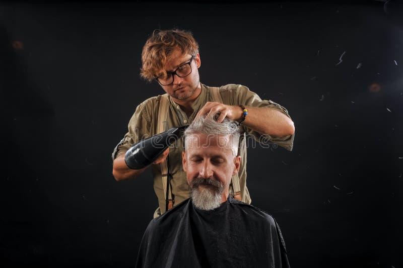 Отрезки парикмахера борода к клиенту к пожилое седому стоковые изображения rf