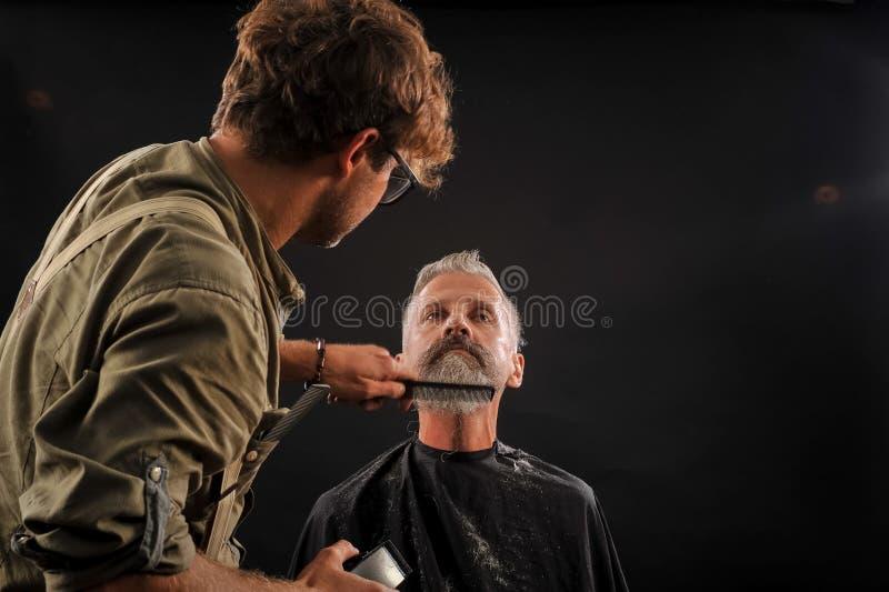 Отрезки парикмахера борода к клиенту к пожилому седому человеку стоковая фотография