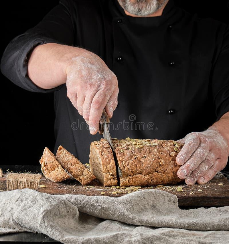 отрезки хлебопека нож в куски хлеба рож с семенами тыквы стоковые фото