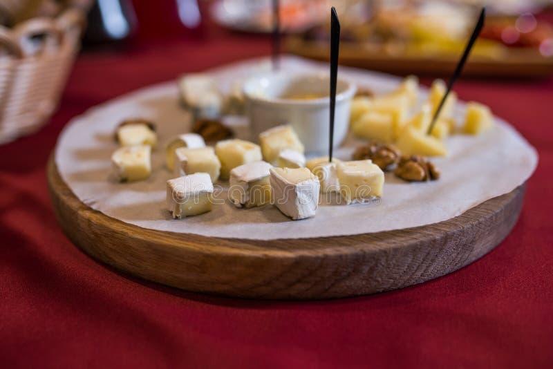 Отрезок сыра камамбера в части на деревянной стойке стоковое фото
