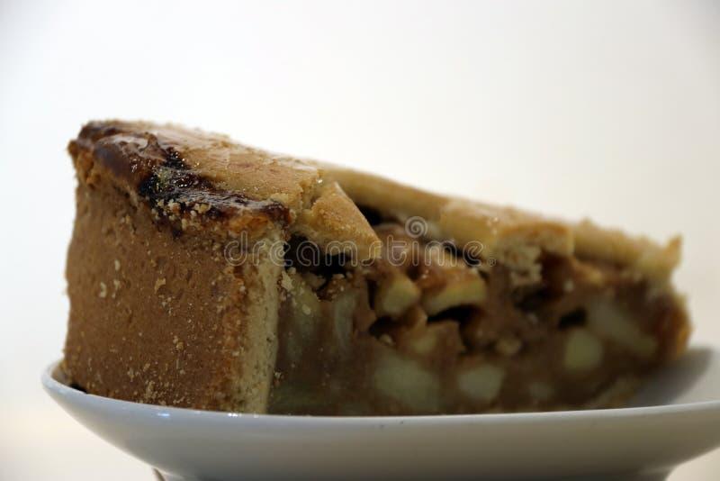 Отрезок торта Яблока триангулярный от большого круглого торта положил в белизну стоковые изображения rf