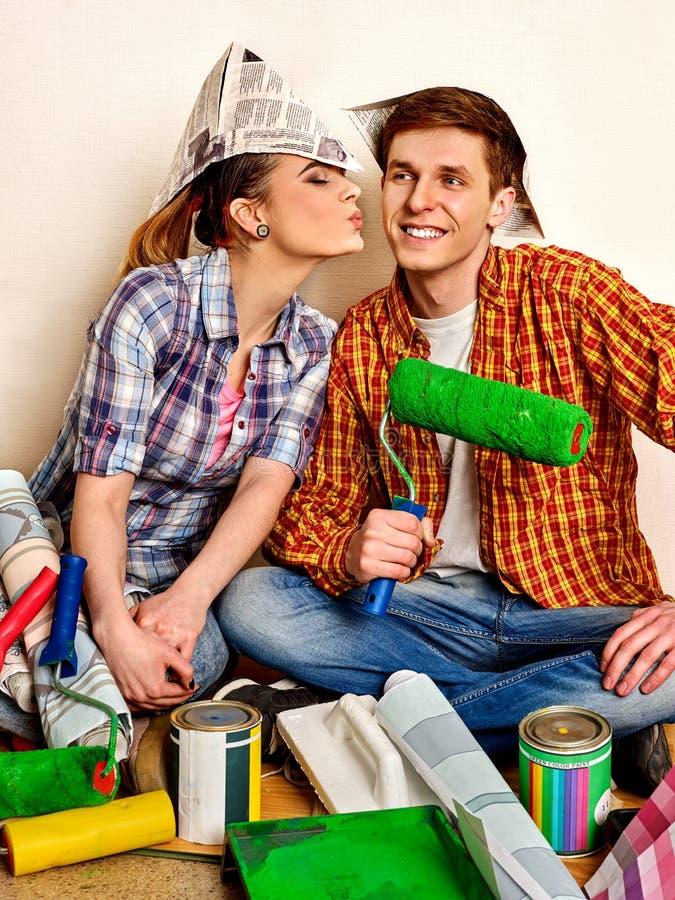 Отремонтируйте семью счастливым домом здания пар используя уровень духа для того чтобы измерить стоковые фото