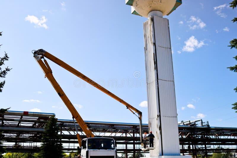 Отремонтируйте столбцы на специальном методе Работники на кране ремонтируют большой белый столбец Косметический ремонт с картиной стоковое фото