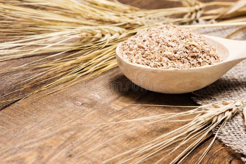 Отруби пшеницы в деревянной ложке с ушами пшеницы стоковое изображение rf