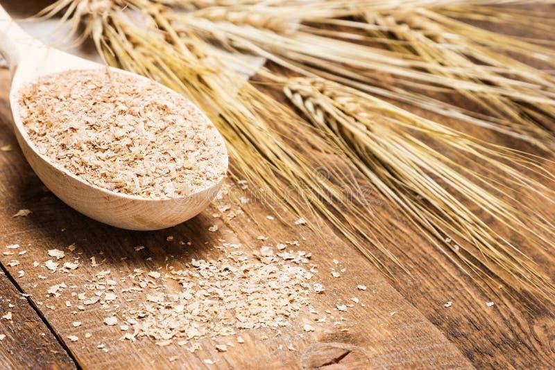 Отруби пшеницы в деревянной ложке с ушами пшеницы стоковая фотография