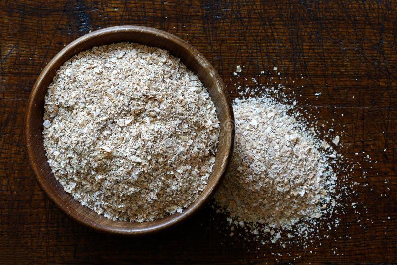 Отруби пшеницы в темном деревянном шаре изолированном на древесине темного коричневого цвета от стоковые фото