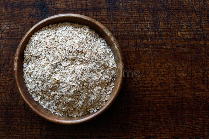 Отруби пшеницы в темном деревянном шаре изолированном на древесине темного коричневого цвета от стоковая фотография rf