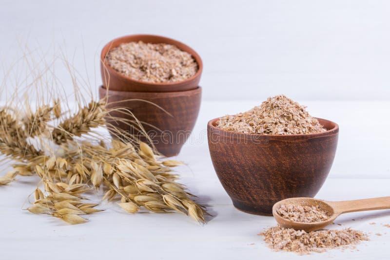 Отруби пшеницы, овса в шаре глины и уши пшеницы и овса Пищевая добавка для того чтобы улучшить пищеварение стоковые изображения