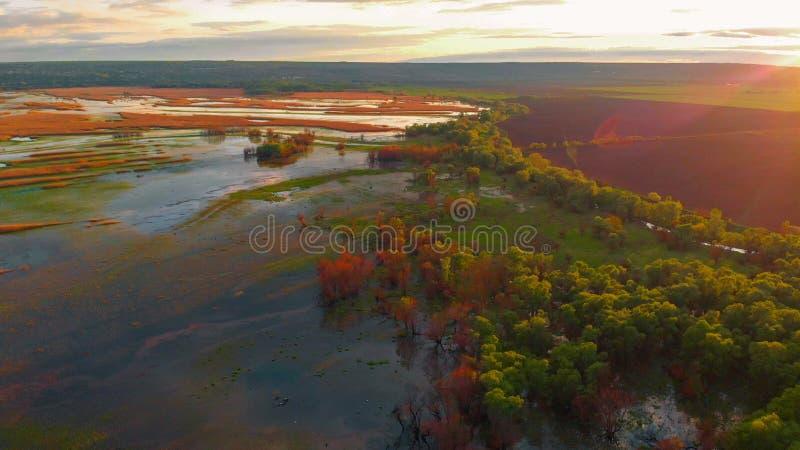 Отснятый видеоматериал трутня воздушного ландшафта реки захода солнца кинематографический Летание над рекой Dniestr в Украине или стоковые изображения rf