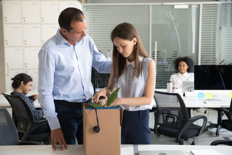Отставка бизнесмена поддерживая осадила пожитки пакета женщины в картонной коробке стоковое изображение rf