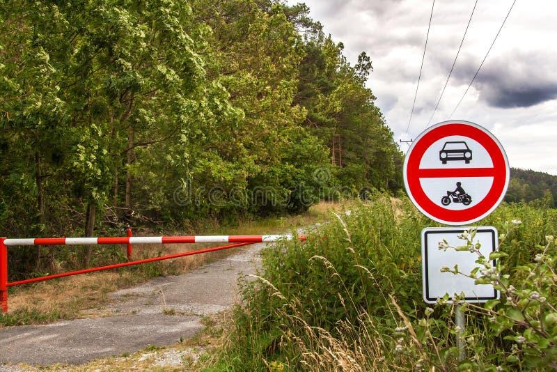 Отсутствие входа для моторных транспортов, задействуя только позволенный Облака шторма над дорогой леса Закрытый вход к дорожному стоковые фото