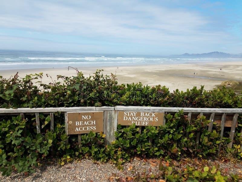 Отсутствие доступа пляжа остаться назад опасным знаком блефа на загородке около пляжа с песком и волнами стоковое фото rf