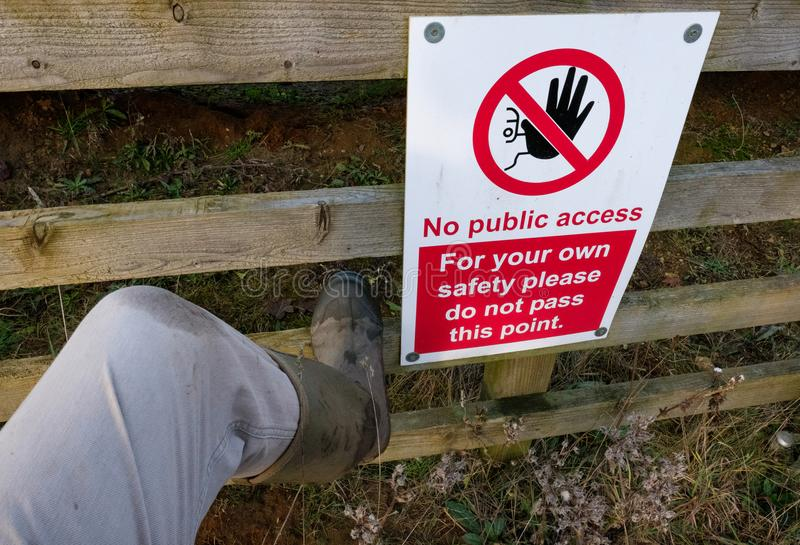 Отсутствие знака доступа на барьере около глубокого карьера, увиденного, что с человеком около взобраться загородка стоковое изображение rf