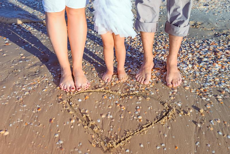 Отсутствие семьи из трех человек стороны стоя около вычерченной формы сердца на влажном песчаном пляже в солнечном свете Счастлив стоковое изображение rf
