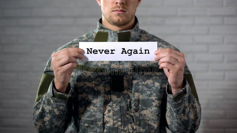 Отсутствие снова слово написанное на знаке в руках солдата, людей против войны стоковое фото rf