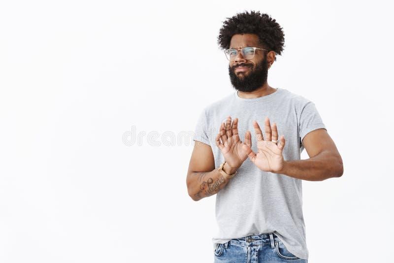Отсутствие спасибо я прохожу Заинтересованный неудовлетворенный Афро-американский мужской клиент с бородой и татуировки гримаснич стоковые фото