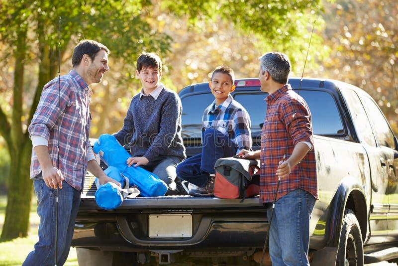 Отцы при сыновьья распаковывая тележку на располагаясь лагерем празднике стоковые изображения rf