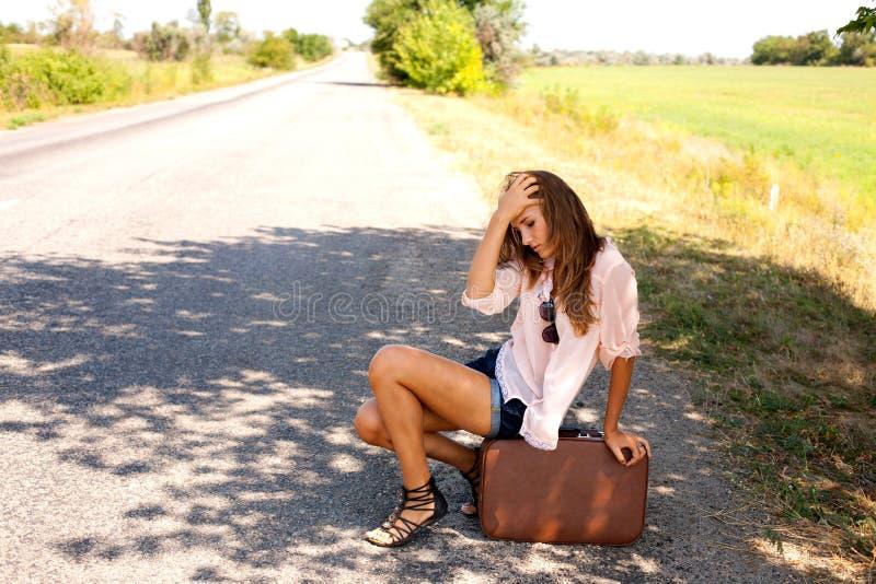 Отчаянная женщина сидя на чемодане стоковая фотография rf