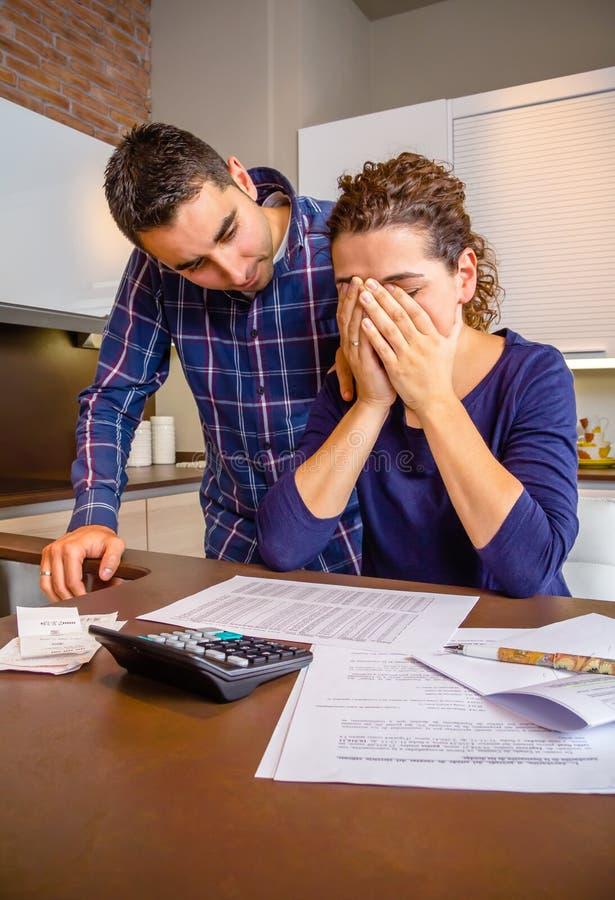 Отчаянная молодая женщина с рассматривать задолженностей стоковое фото