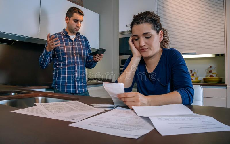 Отчаянные молодые пары при задолженности рассматривая их счеты стоковое изображение rf