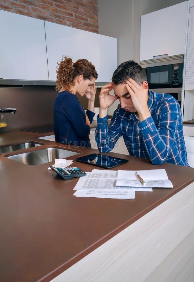 Отчаянные молодые пары с рассматривать задолженностей их стоковая фотография