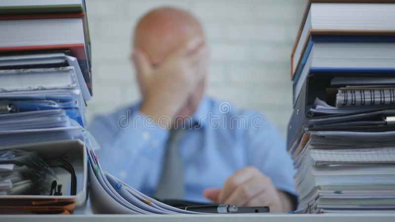 Отчаянный и потревоженный менеджер держа его голову в руках в неясном изображении стоковые изображения rf