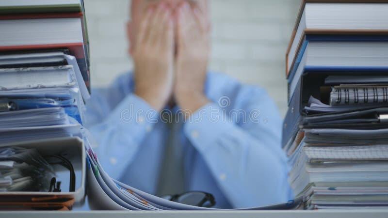 Отчаянный и потревоженный менеджер держа его голову в руках в неясном изображении стоковая фотография