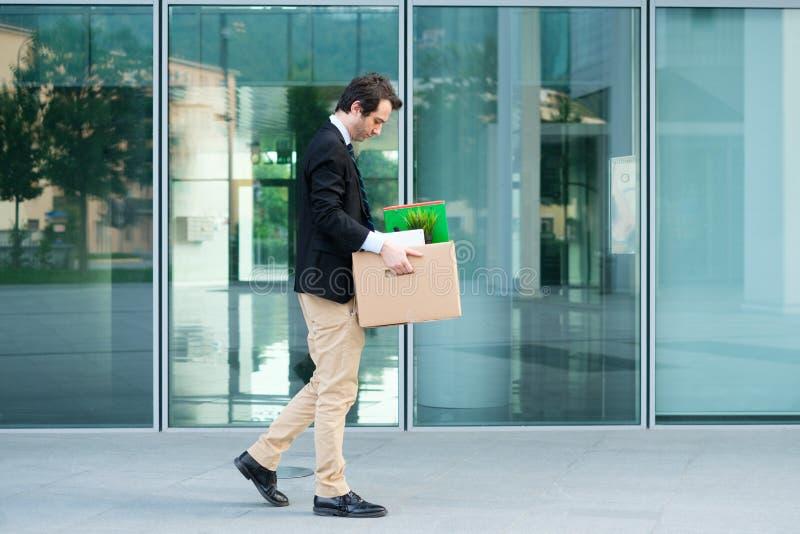 Отчаянный и увольнянный бизнесмен идя далеко от офиса стоковые фотографии rf