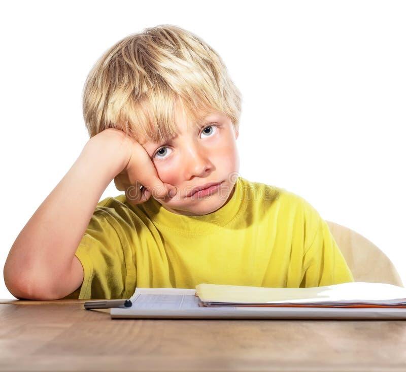 Отчаянный мальчик делая его домашнюю работу стоковое фото rf