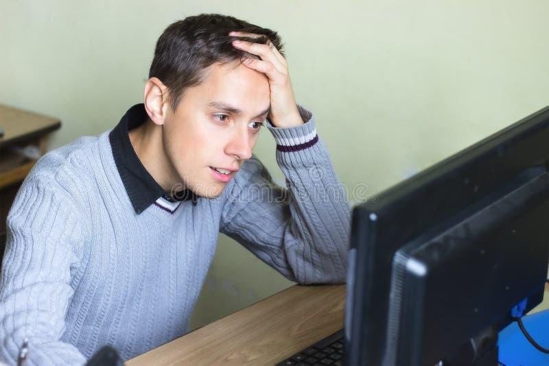 Отчаянный мальчик около компьютера стоковое фото rf