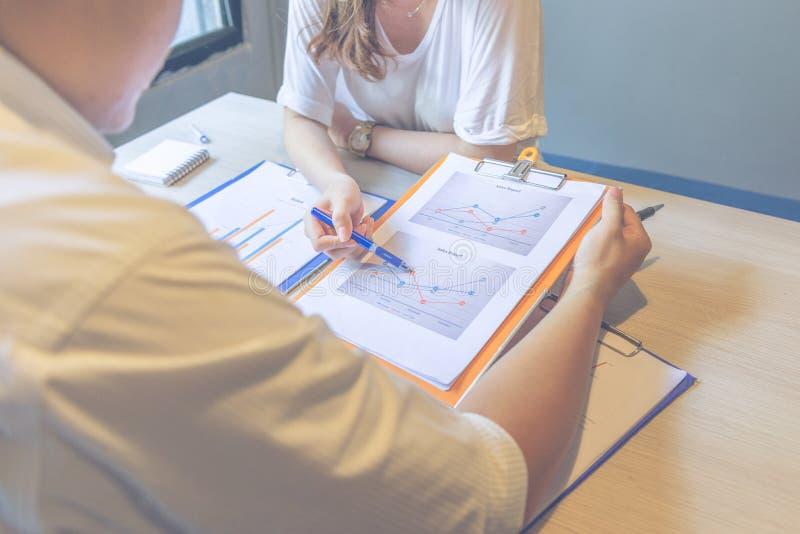 Отчеты о данным по продаж показа коммерсантки к ее партнеру стоковая фотография rf