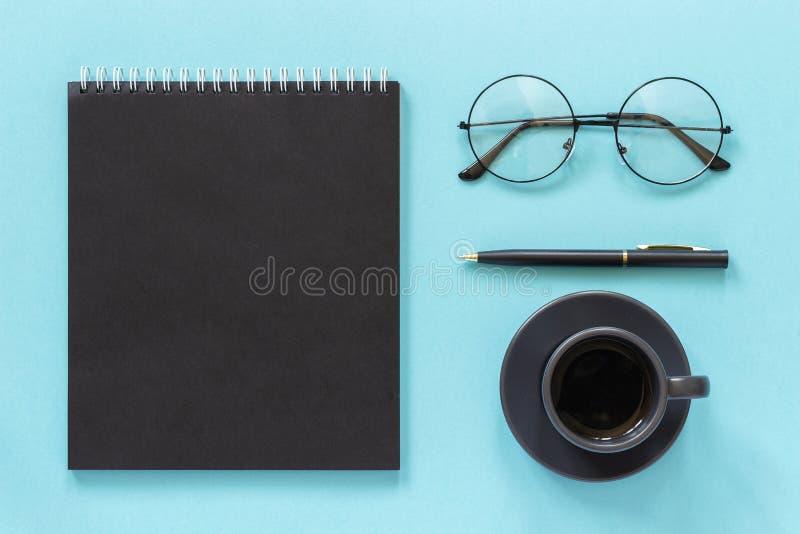 Офис или домашнее рабочее место Черный блокнот цвета, чашка кофе, зрелища, ручка на голубой предпосылке Рабочее место концепции с стоковое фото
