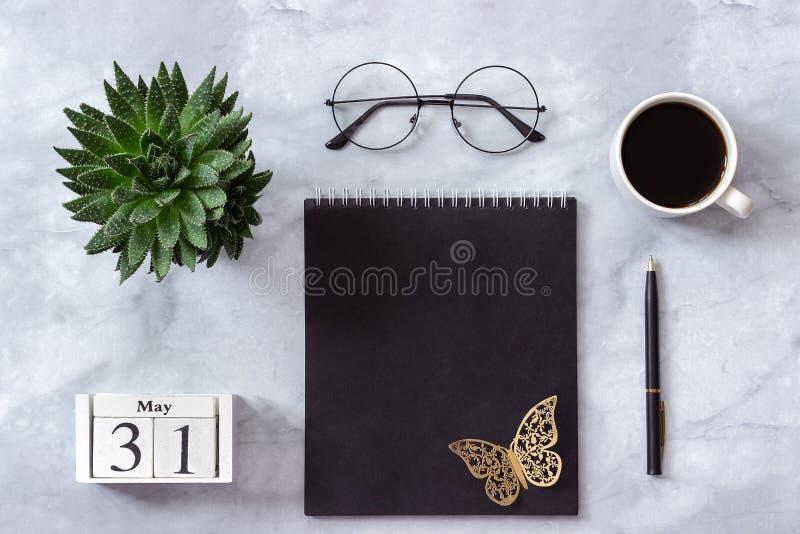 Офис или домашний стол таблицы Деревянный календарь 31-ое мая кубов Черный блокнот, чашка кофе, суккулентная, стекла на мраморной стоковые изображения