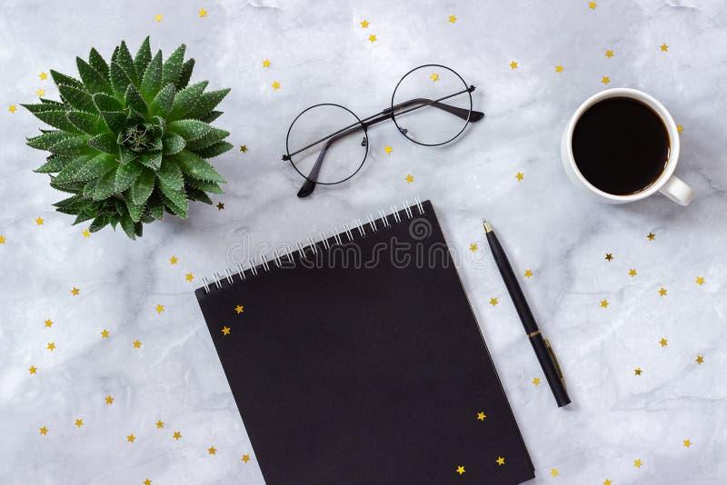 Офис или домашний стол таблицы Черные блокнот, ручка, чашка кофе, суккулентное, стекла и звезды золота на мраморной концепции пре стоковая фотография rf