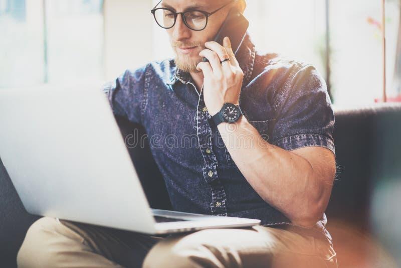 Офис просторной квартиры дизайна интерьера компьтер-книжки мышечного бородатого битника работая современный Человек сидя винтажна стоковое изображение