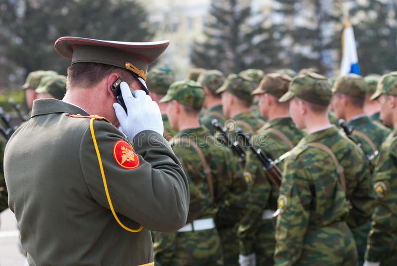 Офицер армии говорит на мобильном телефоне стоковые изображения