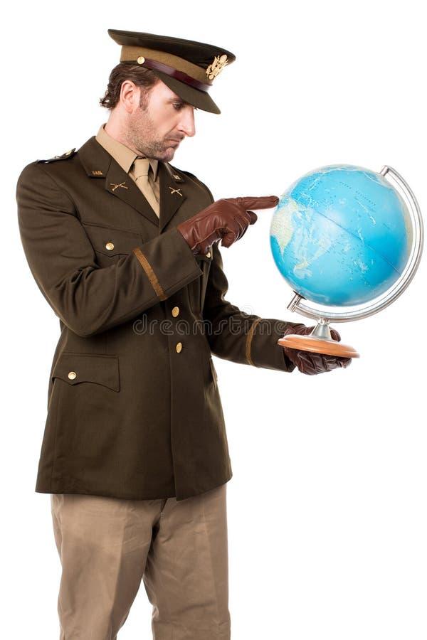 Офицер армии указывая глобус стоковые изображения
