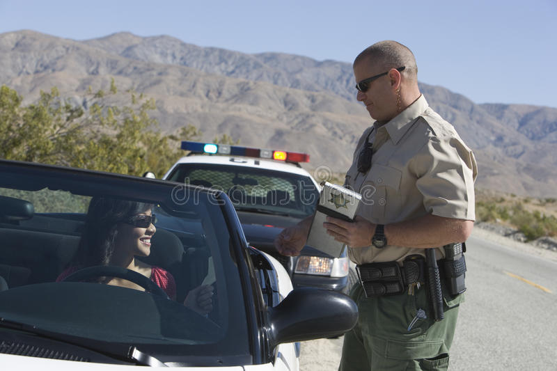 Офицер движения проверяя лицензию женщины стоковое изображение