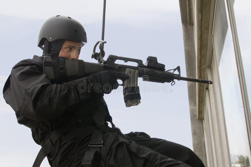 Офицер команды СВАТ Rappelling и направляя оружие стоковое изображение
