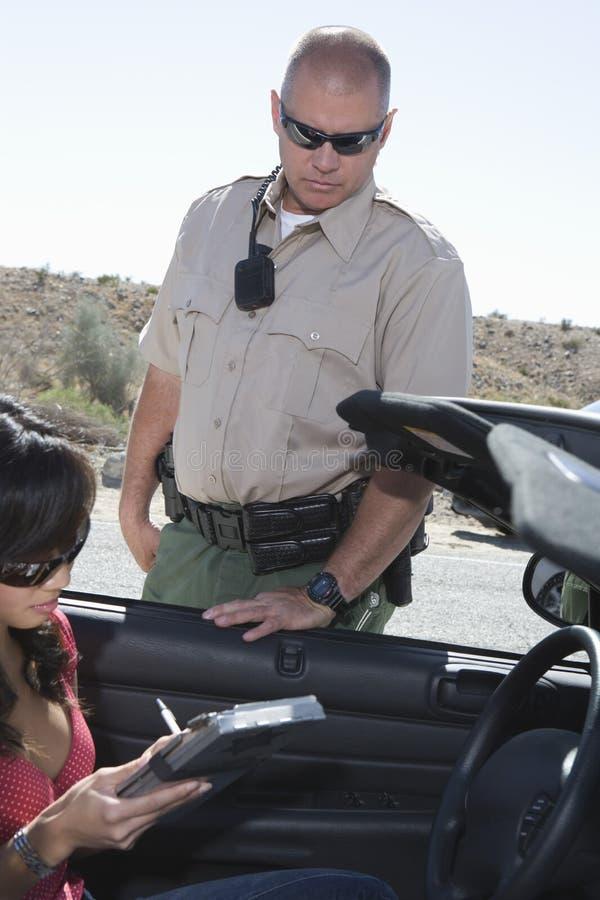Офицер смотря сочинительство женщины на доске зажима стоковое изображение