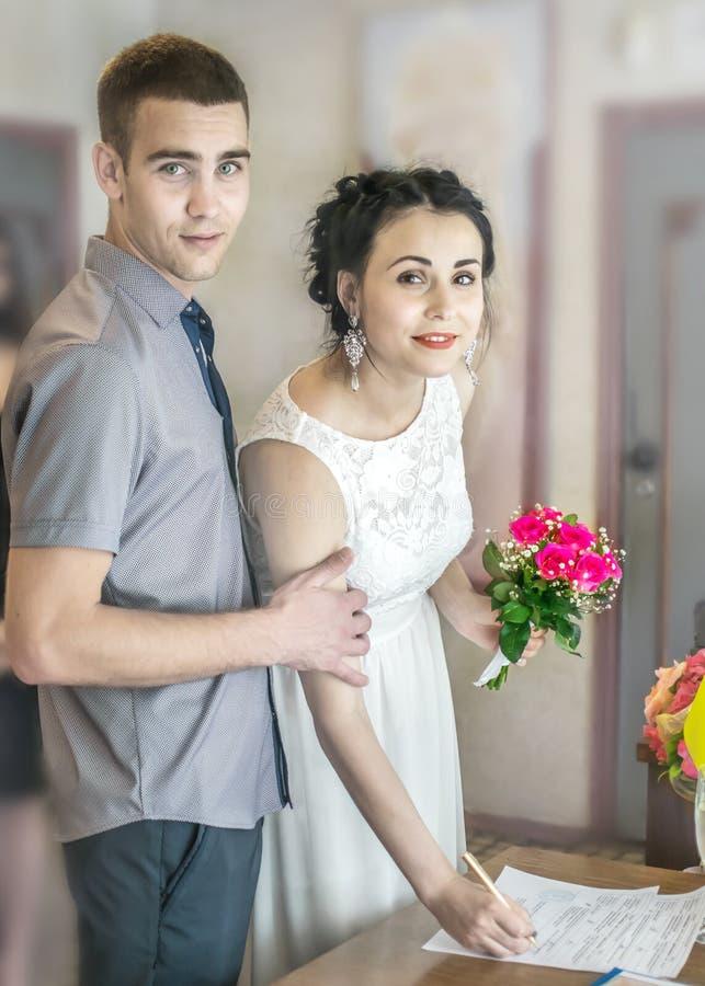 Официальная церемония регистрации замужества в загсе в Украине Молодой красивый жених и невеста пар положил подпись стоковая фотография rf