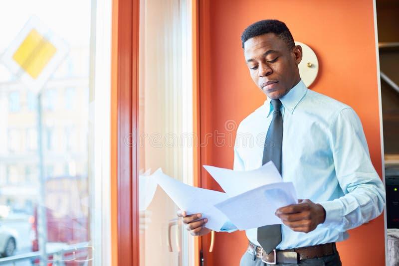Официально черные бумаги чтения бизнесмена стоковая фотография rf